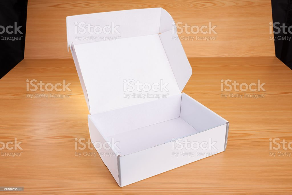 Open blank white box mock up on wood background.