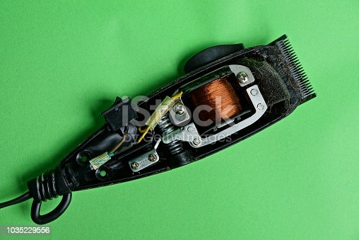 istock Open broken machine for cutting with details on a green table 1035229556
