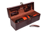 Open brown leather case for wine with a set of tools on white background. Wine opener gift set with bottle of red wine with label in trendy color lush lava. Close-up