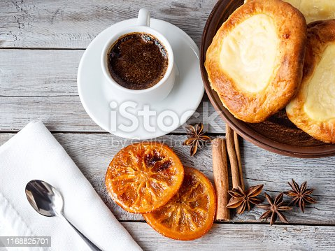 Open buns with cottage cheese (vatrushka)lying in a clay plate on a wooden textural table with a cup of coffee, cinnamon sticks and aniseed stars. Morning still life