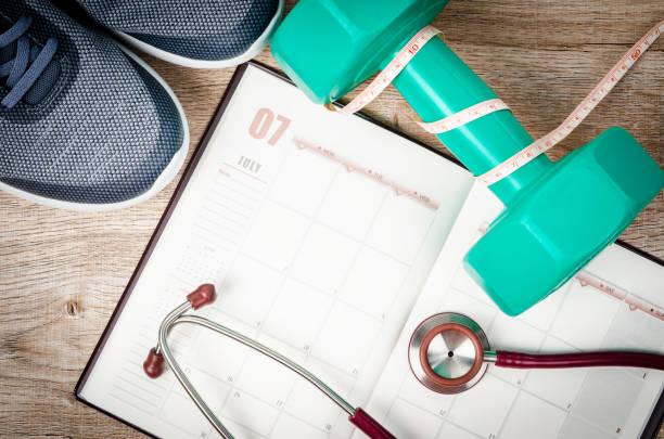 kalender öffnen und hantel mit stethoskop - trainingstagebuch stock-fotos und bilder