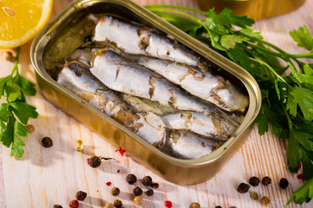 Open can of sardines on table stock photo