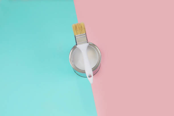 Open can with white paint and brush on color pastel background. stock photo