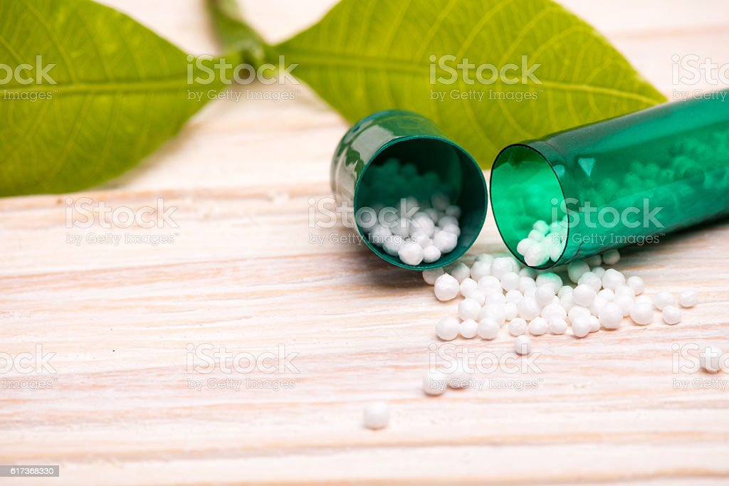 Open capsule with small white balls and green leaf stock photo