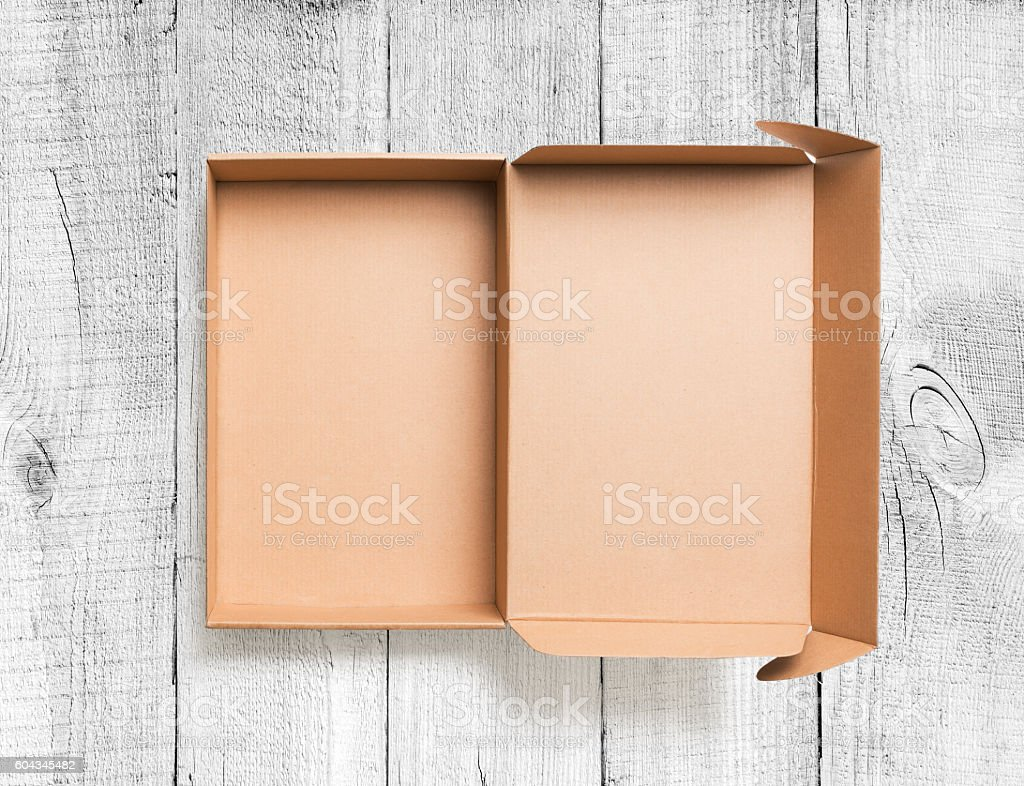 Open cardboard box top view on wooden background stock photo