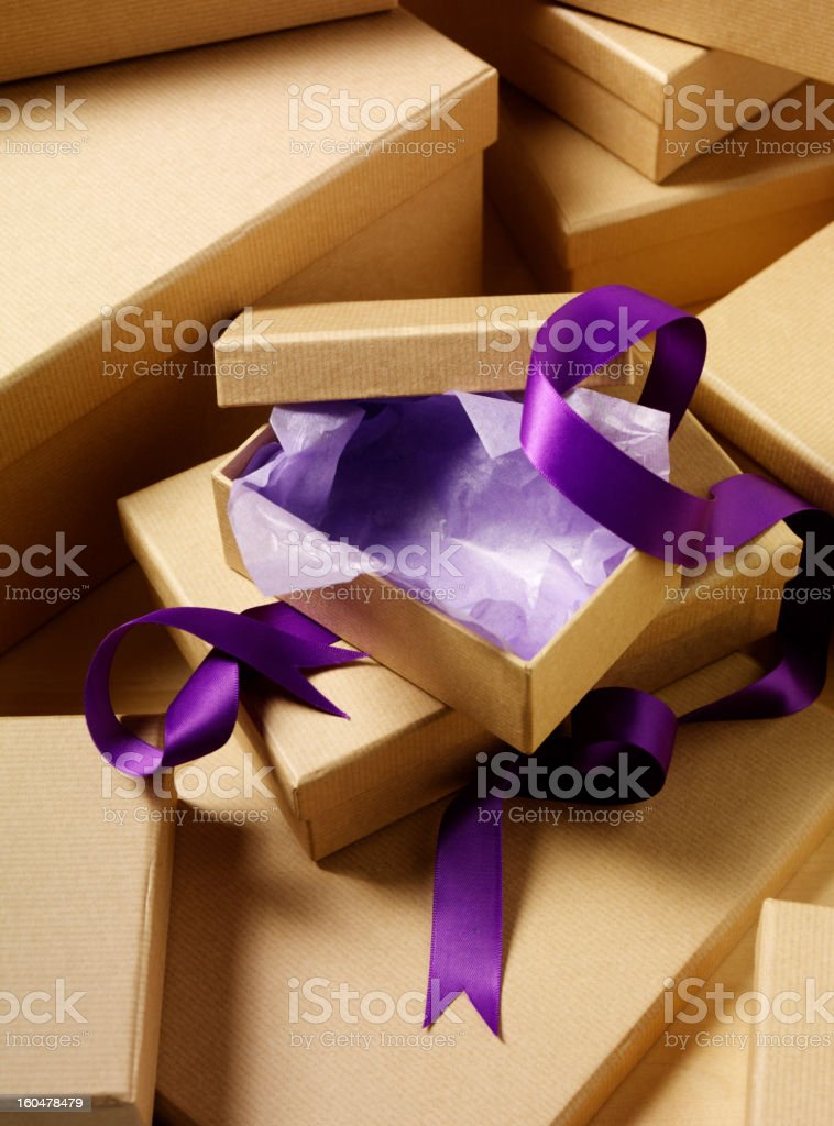 Open Cardboard Box with Purple Tissue Paper and Ribbon royalty-free stock photo