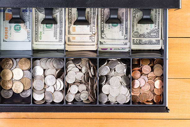 Open cash register drawer on wooden table Top down view on single cash register drawer stocked full with pennies, dimes, nickels, quarters, various American dollar bills over wooden table cash register stock pictures, royalty-free photos & images