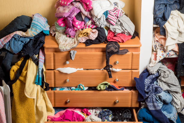 open chest drawers with drop-down clothes and piles of clothes around in a mess.Close-up stock photo