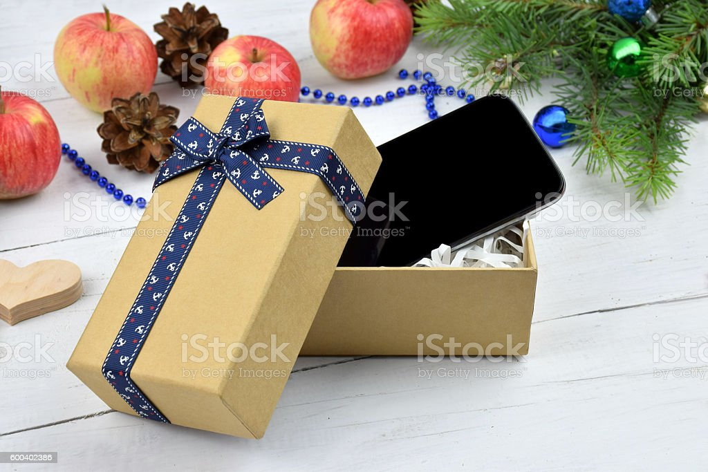 Open Christmas gift box with a smart phone inside, presents and...