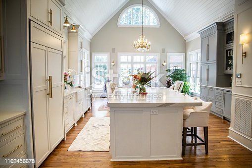 Open Concept Elegant and Spacious Kitchen with Marble Countertops, Chandelier, and Two-Toned Cabinets