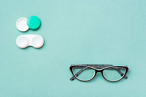 istock Open container with lenses and glasses on a green background 1049292226