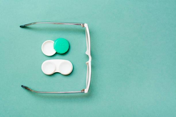 Açık konteyner ile lens ve gözlük yeşil bir arka plan üzerinde stok fotoğrafı