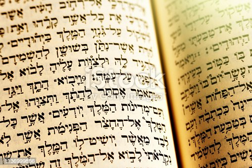 A Hebrew translation of the bible lies open with a gold tinge to the light.