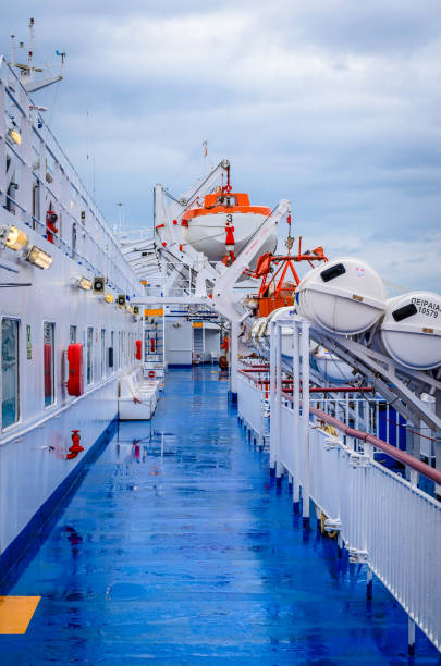 Open deck corridor of a ferry boat with rescue boats and the port of Piraeus in background. stock photo