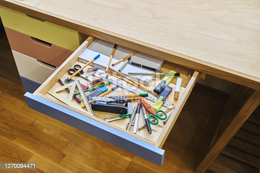 Open drawer of modern desk with unsorted stationery not ready for school studies