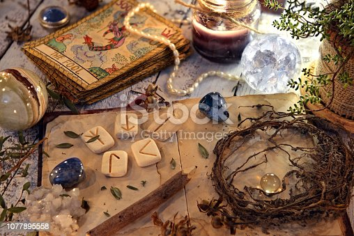 811119304 istock photo Open diary book with runes, dried herbs and tarot cards on table 1077895558