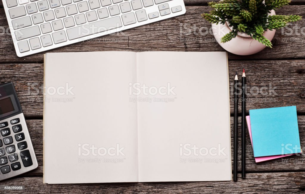 Open diary on wood table with keyboard, hand phone and calculator. stock photo