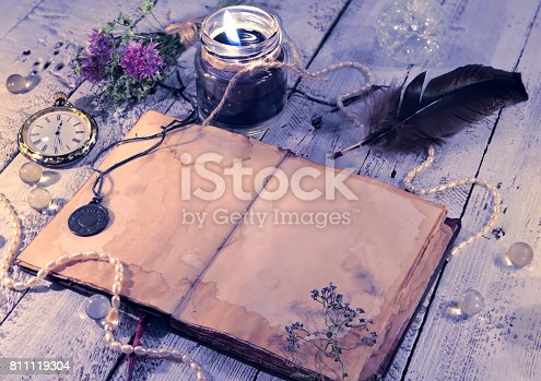 811119304 istock photo Open diary with clock, black candle, quill and medallion 811119304