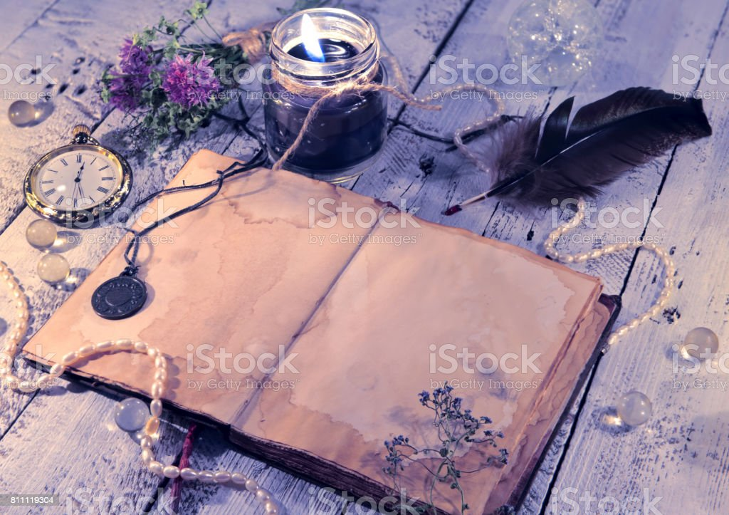 Open diary with clock, black candle, quill and medallion stock photo