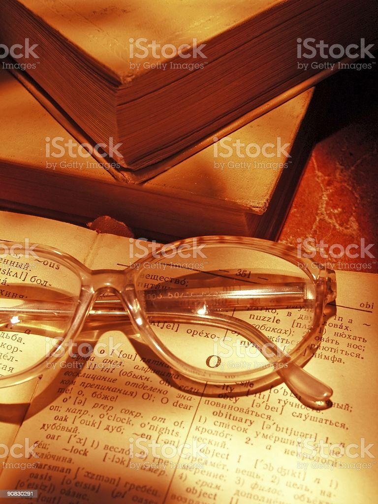 Open dictionary, glasses and books royalty-free stock photo