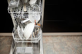 Open dishwasher machine, crockery, dishes, cutlery. Horizontal high angle view with copy space available on the right.