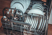 Open dishwasher with clean dishes after cleaning process - selective focus