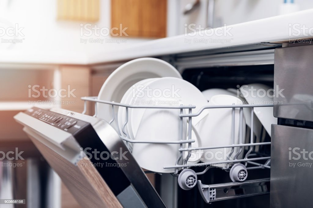 open dishwasher with clean dishes at home kitchen stock photo
