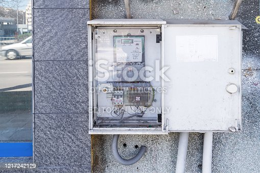 istock Open distribution switchboard with electric meter box on a outdoor wall of the building. View from the street. 1217242129