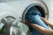 Woman's hand loading dirty blue bed sheets in a white washing machine.