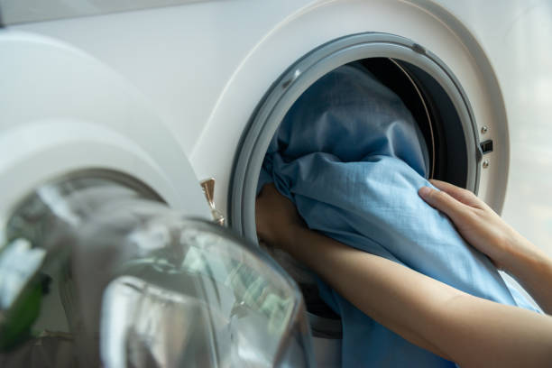 open door in washing machine with blue bed sheets inside close up - sheet imagens e fotografias de stock