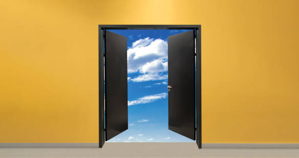 Open door on orange wall background, blue sky with clouds view out of the door stock photo