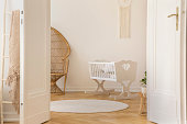 Open door to white scandi kid room with crib and wicker peacock and carpet on the parquet, real photo