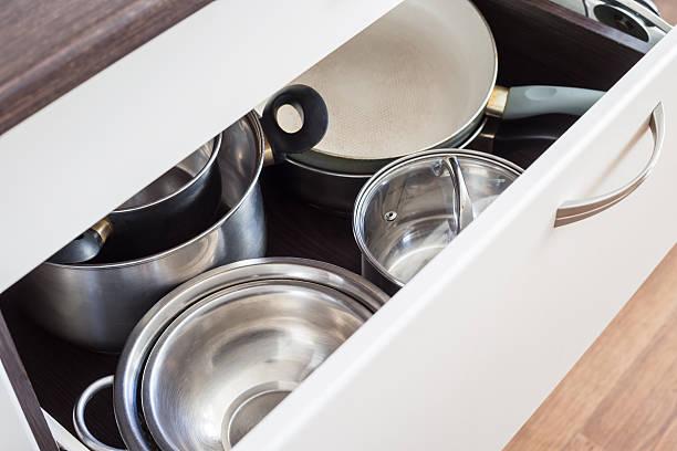 schublade öffnen von schrank mit edelstahl töpfe und pfannen. - topfdeckel speicher stock-fotos und bilder