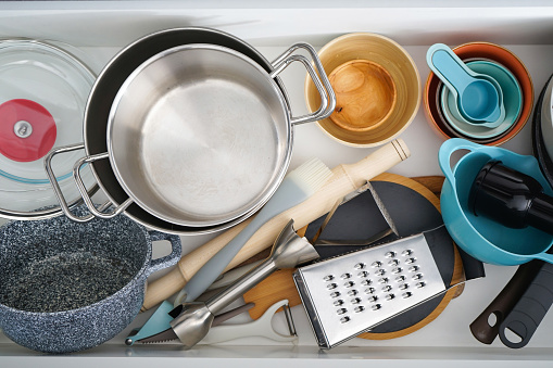 Open drawer with different utensils in kitchen, flat lay.