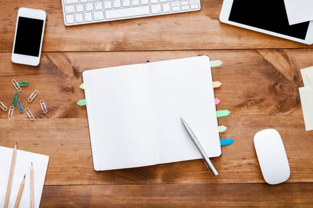 öffnen sie leere leere notebook-organisator mit stift für die planung auf dem arbeitstisch mit geräten und schreibwaren, tablet-telefon liefert tastaturmaus auf braunem holzbüro schreibtisch, top-ansicht von oben - unterrichtsplanung vorlagen stock-fotos und bilder