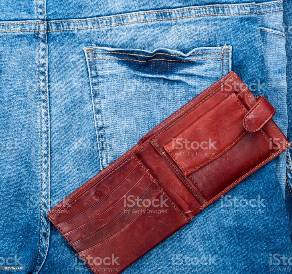 open empty brown leather wallet on the background of blue jeans