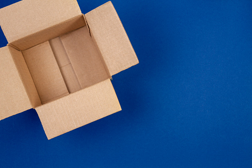 Open empty cardboard boxes on blue background.
