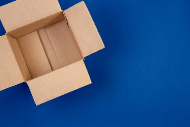 Leere Kartons auf blauem Hintergrund öffnen – Foto