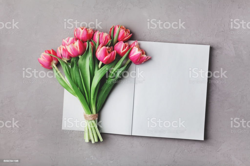 Open empty notebook and bouquet of pink tulip flowers. Woman working desk. Flat lay. stock photo