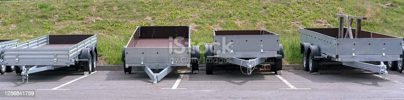 open empty trailers for car cargo truck stands in row outside on parking lot for vehicle rent and sale transport concept