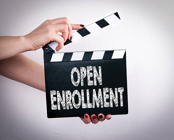 open enrollment. female hands holding movie clapper - open enrollment stock photos and pictures