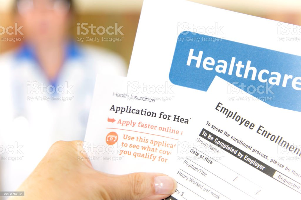 Open enrollment healthcare forms and medical doctor. stock photo