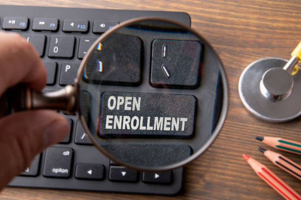 Open Enrollment. Insurance, healthcare, benefits and security concept. Computer keyboard and stethoscope Open Enrollment. Insurance, healthcare, benefits and security concept. Computer keyboard and stethoscope on a wooden table enrollment stock pictures, royalty-free photos & images