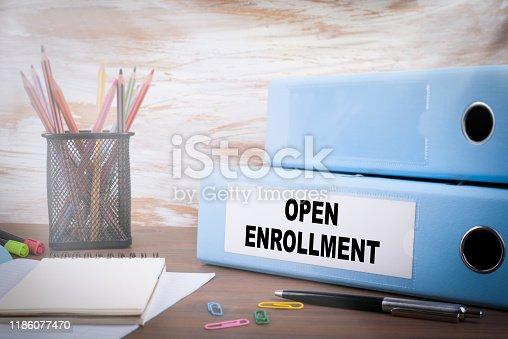 istock Open Enrollment. Office Binder on Wooden Desk 1186077470