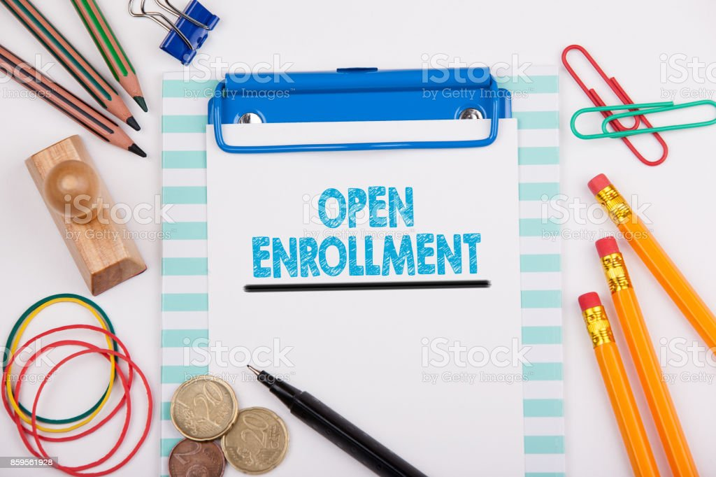 Open Enrollment. White office desk with stationery stock photo