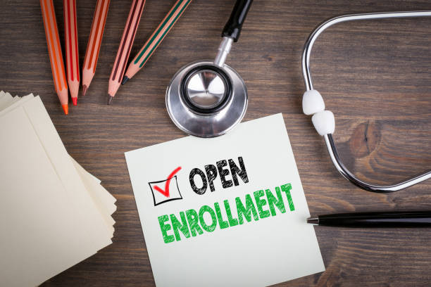 Open Enrollment. Workplace of a doctor. Stethoscope on wooden desk. stock photo