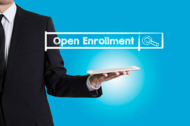 open enrollment, young man holding a tablet computer - open enrollment stock photos and pictures