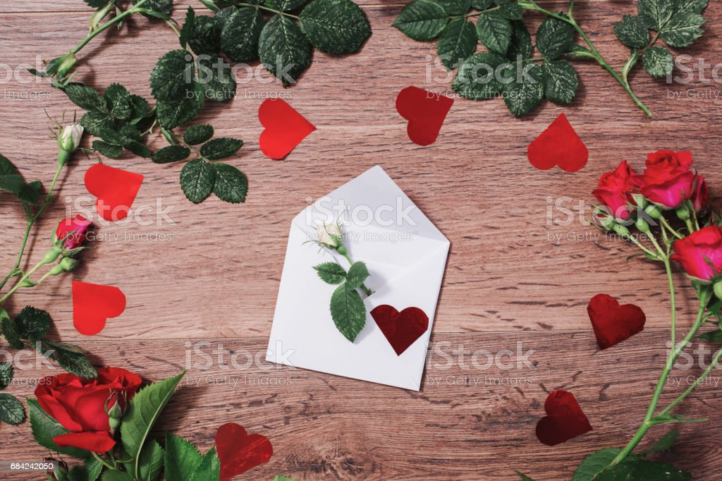 Open envelope, frame of red roses with green leaves and red hearts on a wooden background. Greeting card. Conceptual photography. Wedding invitation card. Valentine day. Flat lay, top view, copyspace royalty-free stock photo