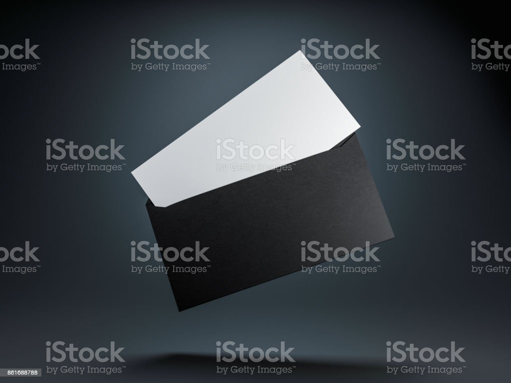 Open envelope with white invitation or letter mockup inside on black background stock photo