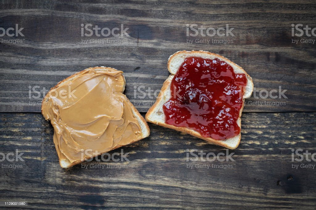 Open face homemade peanut butter and strawberry Jelly sandwich stock photo
